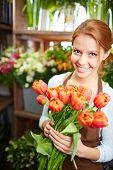 Portrait of young female florist with red tulips looking at camera