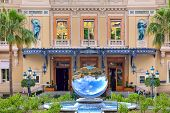 MONTE CARLO, MONACO - JULY 13, 2013: Mirror fountain and facade of famous Casino - gambling and entertainment complex designed by architect Charles Garnier and opened in 1879 (focus on mirror).