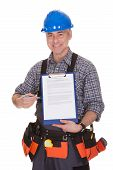 Happy Technician Pointing On Clipboard