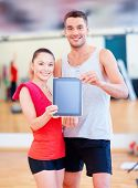 fitness, sport, training, gym and lifestyle concept - two smiling people showing blank tablet pc screen