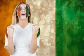 Excited ivory coast fan in face paint cheering against ivory coast flag in grunge effect