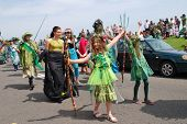 HASTINGS, ENGLAND - MAY 5, 2014: Costumed people take part in a parade on the West Hill during the annual Jack In The Green festival. The festival marks the May Day public holiday in Britain.