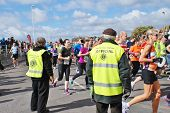 HASTINGS, ENGLAND - MARCH 23, 2014: Marshals watch runners taking part in the annual Hastings Half M