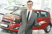 Portrait og salesperson or manager of car automobile dealer welcoming with open arms