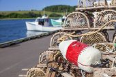 picture of lobster trap  - Piles of lobster traps with buoys on the wharf in rural Prince Edward Island - JPG