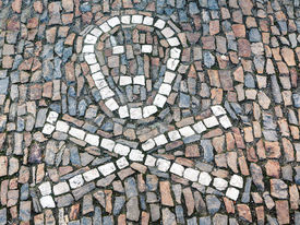 image of head femur  - Symbol of a human skull with two crossed femur bones on the sidewalk built with stone mosaic - JPG