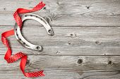 Holidays background with horseshoe and red ribbon on old wooden