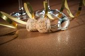 Cork from champagne bottle and two glasses on golden background