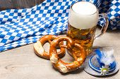 Bavarian beer mug and pretzels on a rustic wooden table