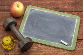 stock photo of red barn  - blank slate blackboard sign against weathered red painted barn wood with a dumbbell - JPG