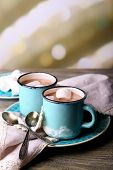 Cups of tasty hot cocoa, on wooden table, on light background