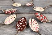 Spoons with tasty chocolate for party on old wooden table