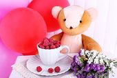 Toy bear, balloons and cup of raspberries on wooden wall background