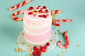 Cranberry milk dessert in glass jar, on color wooden background