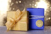 Blue and golden gift boxes on table on shiny background
