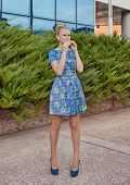 Young girl blonde in blue short dress eats pie
