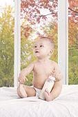 Baby Girl With Milk Bottle On Bedroom