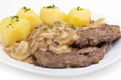 fried steak with mushrooms, potatoes, sauce and parsley