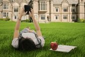 Girl Lying On Grass And Texting With Cellphone