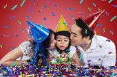 Two Parents Kiss Their Child In Birthday Party