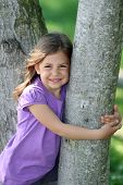 Girl hugging tree trunk