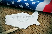 a piece of paper in the shape of United States with the word Veterans Day on a wooden background with the flag of the United States in the background