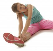 Fit young woman stretching her leg to warm up isolated