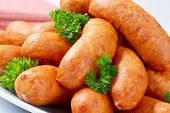 detail of smoked pork mini sausages decorated with parsley