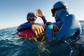 Free diver showing ok signal after deep dive to his safety buddy