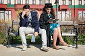 Young Retro Couple In Quarrel Sitting On Bench Reading Book