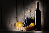 Still life with a bottle wine and  basket of fruit