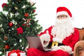 technology, holidays and people concept - man in costume of santa claus with laptop computer, gifts and christmas tree sitting in armchair