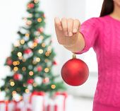 christmas, decoration, holidays and people concept - close up of woman in pink sweater holding christmas ball over living room and tree background