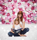 childhood, parenting, people and education concept - happy mother with little girl reading book over wooden floor and flowers background