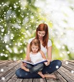 childhood, parenting, people and education concept - happy mother with little girl reading book over wooden floor and green plants background