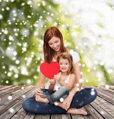 childhood, parenting, love and people concept - happy mother with little girl and red heart over wooden floor and green plants background