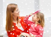 family, childhood, holidays and people concept - happy mother and daughter with comb at home