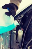 transportation, winter and vehicle concept - closeup of man pouring antifreeze into windscreen water tank