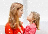 family, childhood, holidays and people concept - happy mother and daughter kissing at home