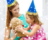 family, childhood, holidays and people concept - happy mother and daughter in blue party hats with teddy bear toy