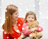 family, childhood, holidays and people concept - happy mother and daughter with teddy bear toy