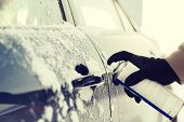 transportation, winter and vehicle concept - closeup of man hand with lock door de-icer