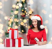 christmas, shopping and people concept - smiling woman in santa helper hat with gift boxes, laptop computer and credit card over tree lights background