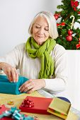 Senior woman wrapping gifts for christmas with wrapping paper