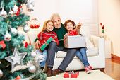 Two children sitting with gifts and grandfather at christmas on the sofa