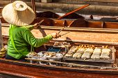 image of peddlers  - Hawkers selling fruits and vegetables in the traditional floating market in Damnoen Saduak near Bangkok Thailand - JPG