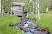 Meadow, wooden barn and a stony creek, brook.