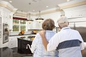 pic of rebuilt  - Happy Senior Couple Looking Over Beautiful Custom Kitchen Design - JPG