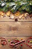 Christmas wooden background with snow fir tree, spices, gingerbread cookies and candies. View from above with copy space