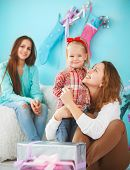 Portrait Of A Mother With Baby Daughter And Teen Daughter Near The Christmas Tree